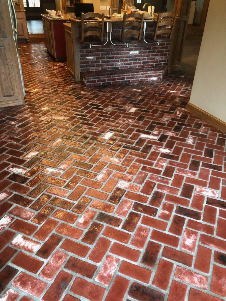 Patriot Pavers thin brick veneer. Brick floor in a kitchen. Sadie's Vineyard brick color.  Alpha Brick Antique Burgundy brick color.